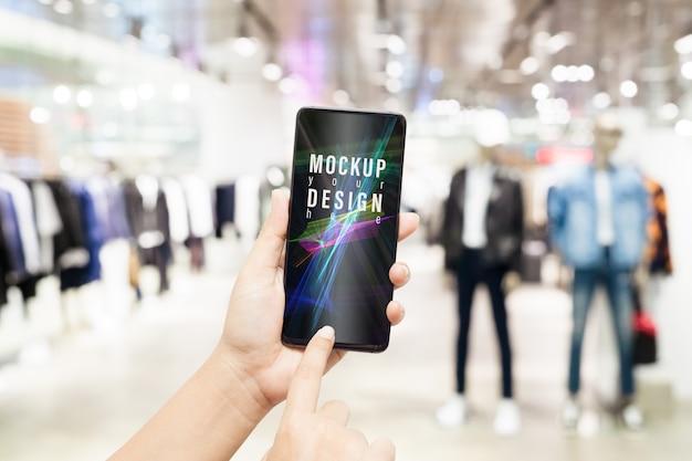 Smartphone del modello con il negozio di abbigliamento maschio vago