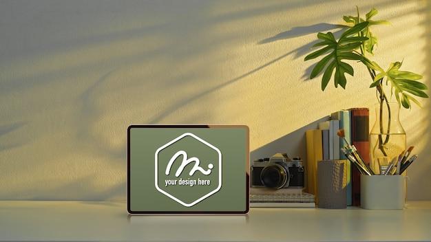 Mockup tablet sul tavolo di studio con copia spazio, fotocamera e elementi di scuola in ufficio a casa