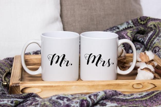 Mockup di due tazze di caffè bianco su un vassoio di legno in interni accoglienti