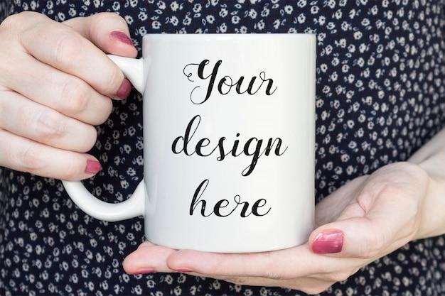 Mockup di una tazza di caffè bianco nelle mani di donna