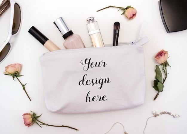Mockup di una borsa cosmetica in cotone bianco con cosmetici all'interno