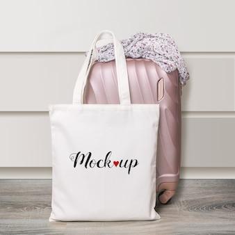 Mockup di una borsa ecologica in cotone bianco con valigia da viaggio