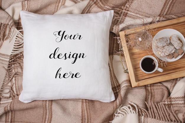Mockup di un cuscino bianco, cuscino su un plaid
