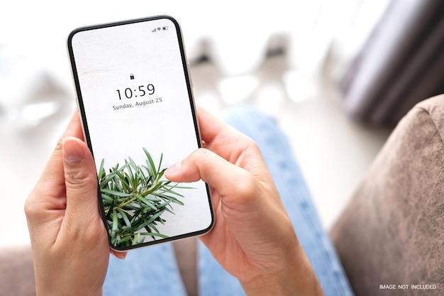 Mano della donna del modello che tiene lo smart phone nero con lo schermo bianco in bianco sul sofà a casa. concetto di business e tecnologia