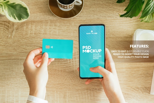 Mockup di una donna che tiene un telefono e una carta di credito sul tavolo