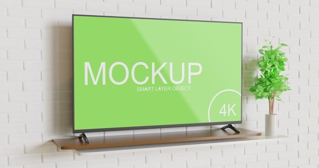 Mockup di tv moderna sul tavolo contro il muro di mattoni