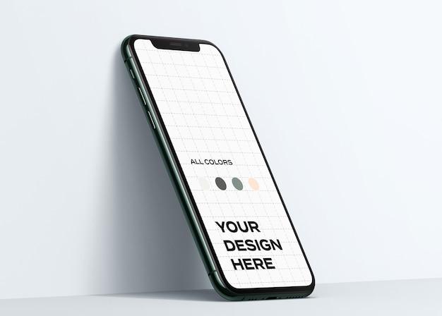 Nuovo smartphone mockup appoggiato al muro