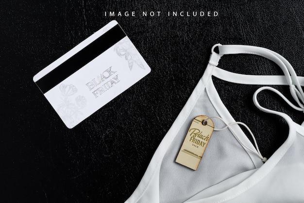 Nuovi vestiti da donna e carta di credito d'oro su sfondo nero