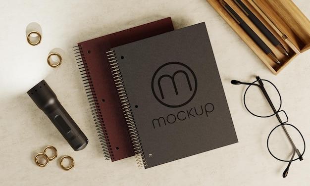 Mockup logo blocco note con occhiali e penne