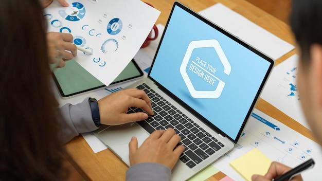 Impiegati che lavorano insieme al laptop mockup e grafico aziendale sul tavolo da riunione