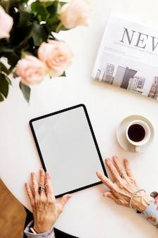 Vecchia donna che utilizza una tavoletta digitale in un mockup di caffè