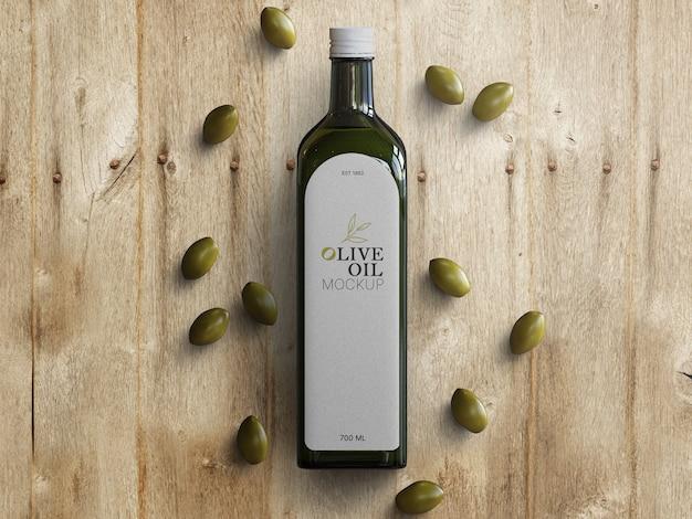 Mockup di bottiglia di vetro di olio d'oliva con olive sparse sul tavolo di legno