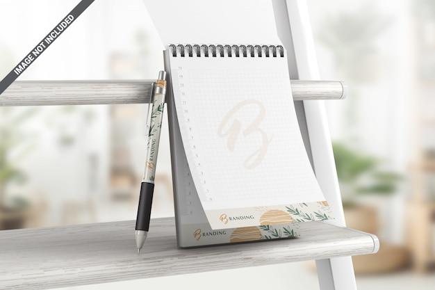 Apra il taccuino con la penna su un modello dello scaffale