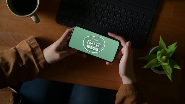 Scatto dall'alto delle mani femminili che tengono mock up smartphone orizzontale sulla tavola di legno