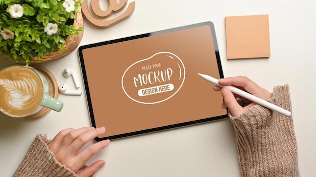 Scatto dall'alto di mani femminili utilizzando il modello di tavoletta digitale con penna stilo sulla scrivania bianca, vista dall'alto