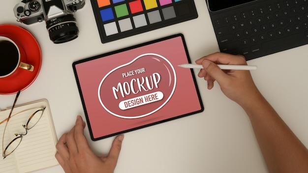 Scatto dall'alto del designer maschio che lavora con mock up tablet