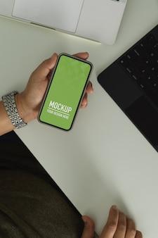 Scatto dall'alto del lavoratore di ufficio maschio utilizzando smartphone include il tracciato di ritaglio sul tavolo da lavoro