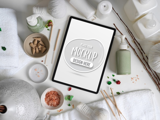 Scatto dall'alto di mock up tablet digitale sul tavolo bianco con accessori spa, asciugamani e decorazioni