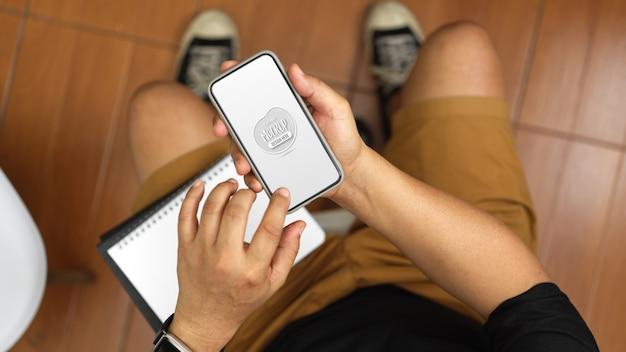 Scatto dall'alto del giovane che lavora alla sua idea mentre tocca mock up smartphone nella sua stanza