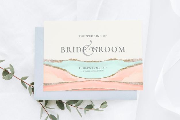 Dipingi la partecipazione di nozze testurizzata con foglie mockup