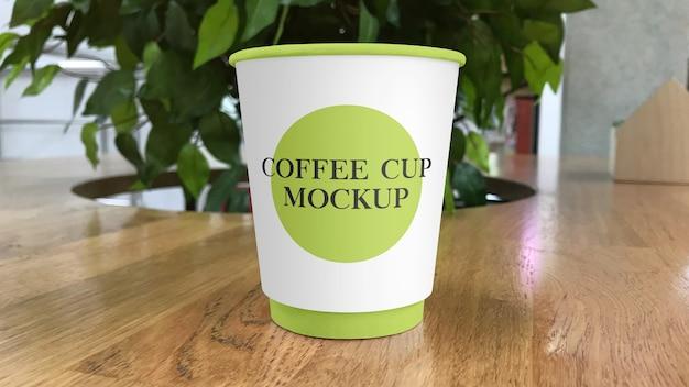 Tazza di caffè di carta sul mockup del tavolo del bar