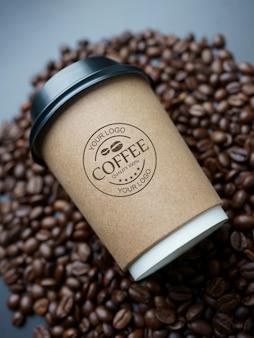 Mockup di tazza di caffè di carta sui chicchi di caffè