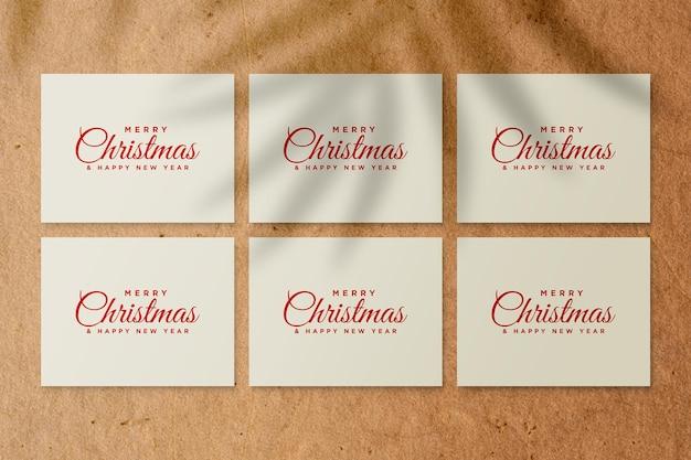Modello di biglietto di auguri di carta con elementi natalizi con ombra di foglie di palma