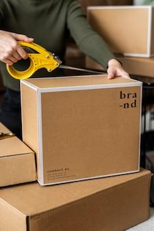 La scatola dei pacchi psd viene imballata per la consegna da un piccolo imprenditore
