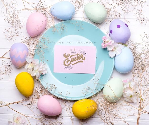 Uova di pasqua di colore pastello su un piatto con mockup di carta