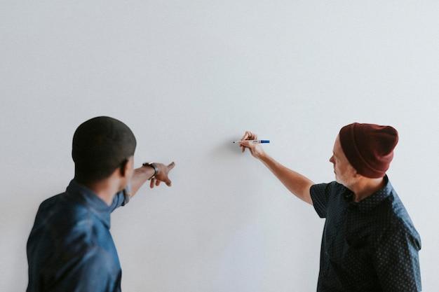 Persone che scrivono su un mockup di muro bianco