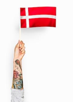 Persona che sventola la bandiera del regno di danimarca