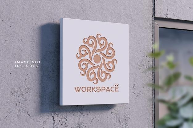 Targa con logo in prospettiva sul muro di cemento - mockup