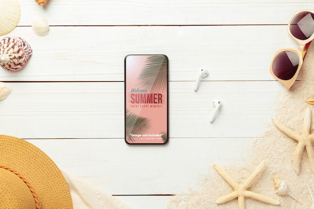 Telefono mockup e accessori da spiaggia sul tavolo di legno bianco.