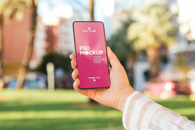 Mockup di schermo del telefono tenuto a mano sulla strada della città