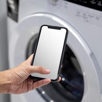 Schermo del telefono mockup psd che controlla elettrodomestici intelligenti e lavatrice