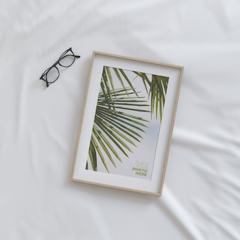 Mockup di cornice con gli occhiali sul letto
