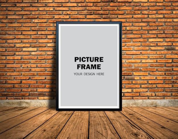 Mockup di cornice per foto appoggiata al muro di mattoni