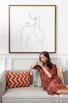 Modello di cornice per foto con in mano una tazza di caffè