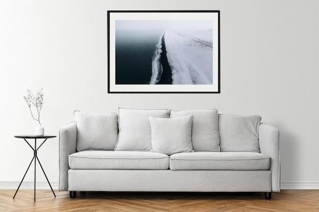 Mockup da parete con cornice per foto psd con una poltrona moderna in un soggiorno dall'arredamento minimal