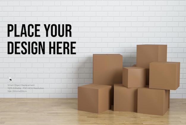 Pila di scatole di cartone con design mockup muro di mattoni bianchi