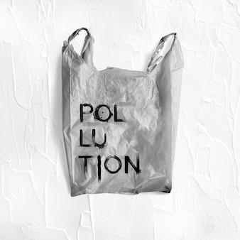 Parola di inquinamento scritta su un modello di sacchetto di plastica grigio