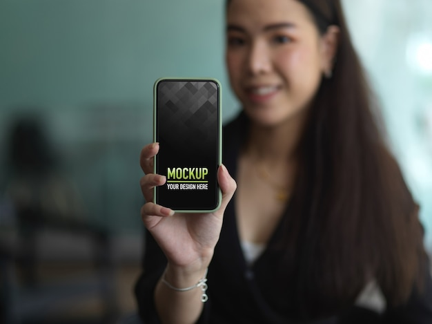 Ritratto di donna in abito nero mano che tiene smartphone per mostrare mock up schermo