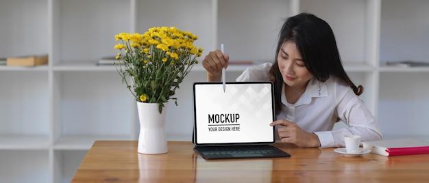 Ritratto di donna che presenta con mock up tablet digitale e accessori