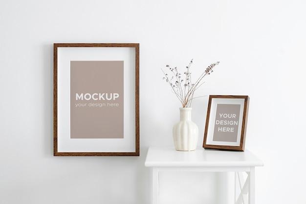 Mockup di cornici per ritratti su parete bianca e mobili con piante secche in vaso
