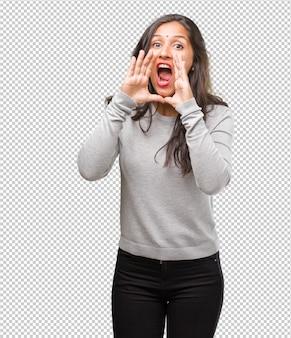 Ritratto di giovane donna indiana urlando felice, sorpreso da un'offerta o una promozione, spalancata, saltando e orgoglioso