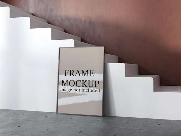 Mockup di cornice per poster appoggiata contro la scala bianca