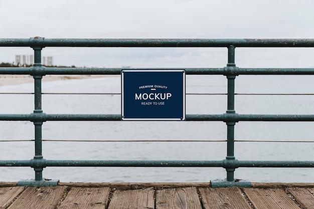 Mockup di bordo di qualità premium su una recinzione vicino alla spiaggia Psd Premium
