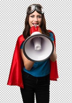 Ragazza graziosa del supereroe che grida dal megafono
