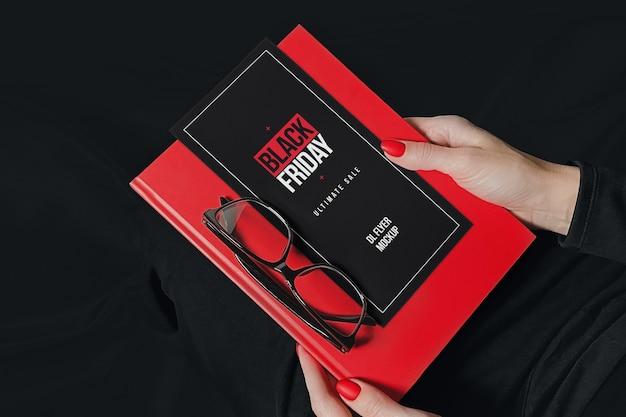 Volantino promozionale con notebook e occhiali in mockup di mani di donna