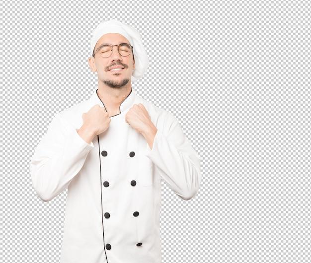 Orgoglioso giovane chef che fa un gesto di forza con il braccio